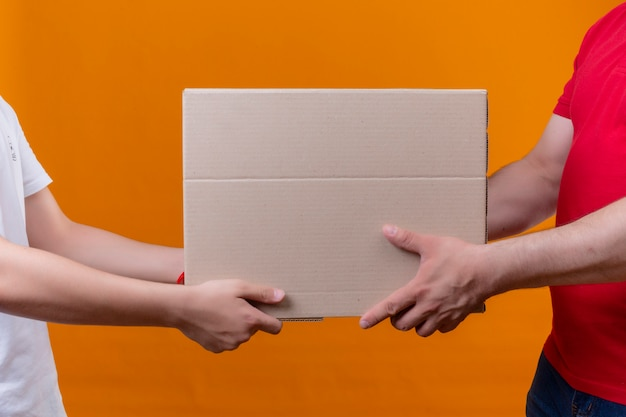 Delivery man in red uniform giving box package to a customer over isolated orange wall Free Photo
