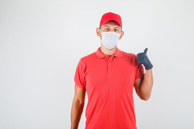 Fattorino in uniforme rossa, mascherina medica, guanti che mostrano qualcosa con il dito Foto Gratuite