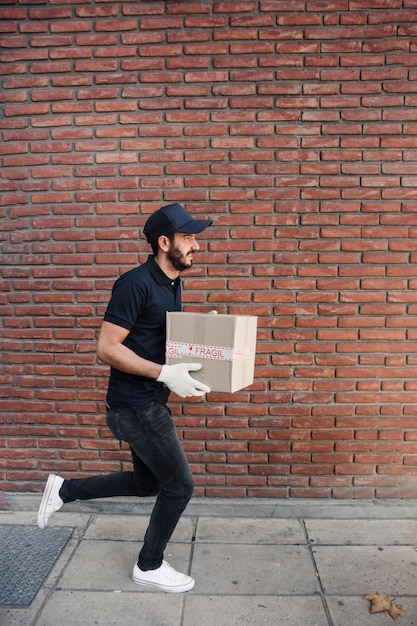 Delivery man running with parcel in front of brickwall Free Photo