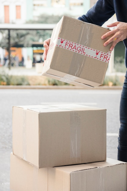 Delivery man's hand carrying parcel Free Photo