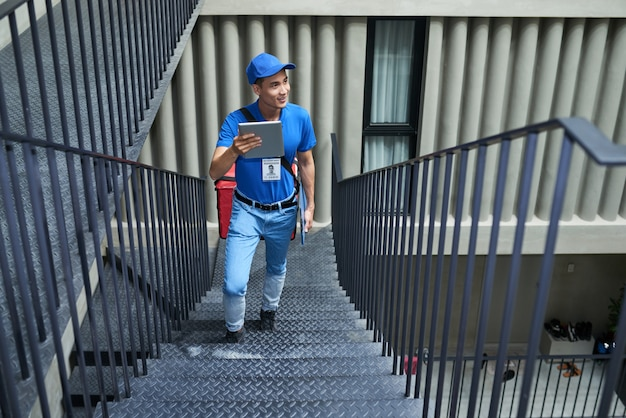 Delivery man searching for right apartment in building Free Photo