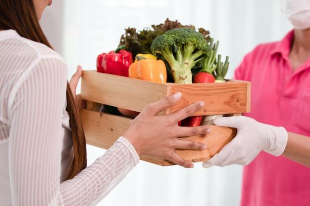 新鮮な有機果物や野菜の木箱を送る配達人 Premium写真