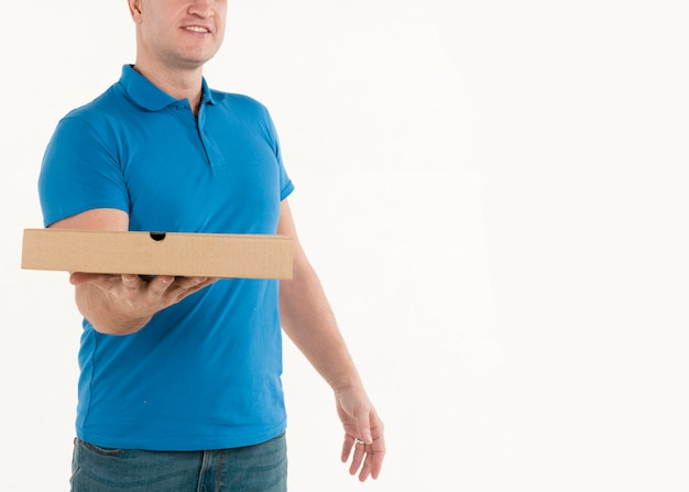 Delivery man showing pizza box held in hand Free Photo