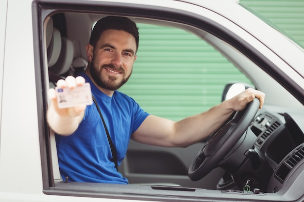Delivery man sitting in his van while showing his driving licence Premium Photo