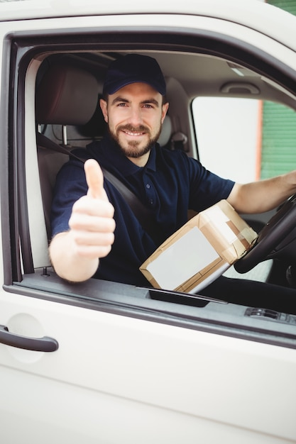 Delivery man sitting in his van with thumbs up Premium Photo