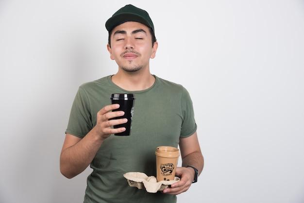 Доставщик, пахнущий ароматом кофе на белом фоне. Бесплатные Фотографии