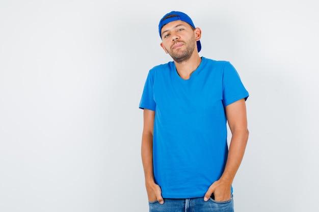 파란색 티셔츠에 주머니에 손을 서 배달 남자 무료 사진