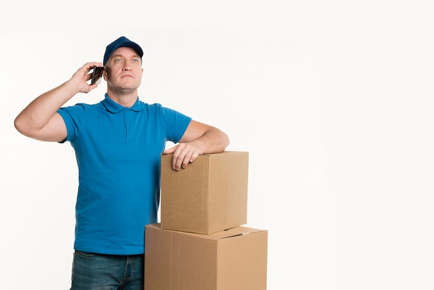 Delivery man talking on phone and posing with cardboard boxes Free Photo