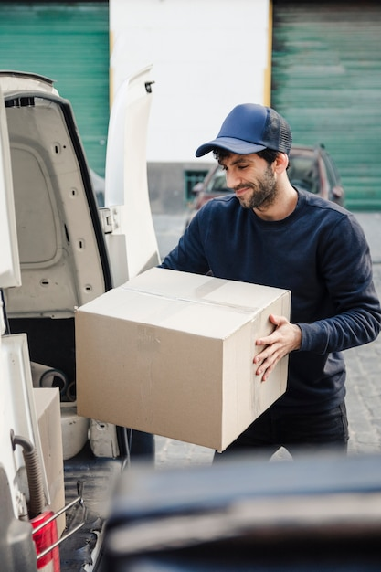 Delivery man unloading cardboard box from vehicle Free Photo