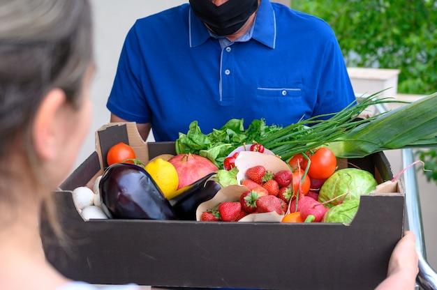 Доставка человек в маске и держит коробку с овощами Бесплатные Фотографии