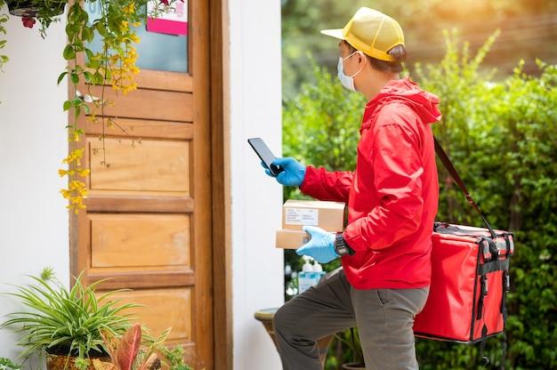 青い手袋と赤いジャケットを着て、携帯電話で顧客の住所を検索する配達人 Premium写真