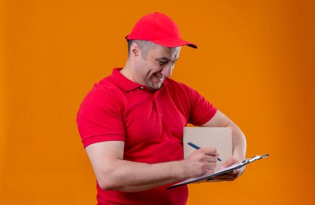 赤い制服を着た配達人とキャップパッケージボックスと元気に立っているスペースを笑顔のペンでクリップボードを保持している配達人 無料写真