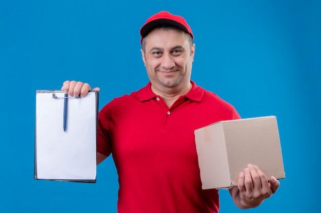 赤い制服を着た配達人と青いスペースの上に立って笑顔で自信を持って探しているブランクのクリップボードを示す段ボール箱を保持しているキャップ 無料写真