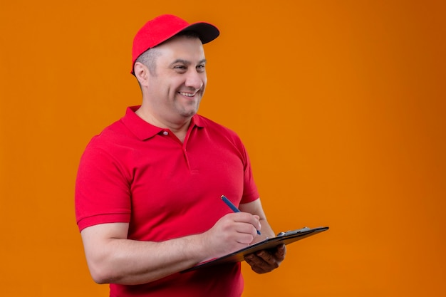 赤い制服を着た配達人とキャップを保持しているクリップボードをよそ見肯定的で幸せな何か立っている笑顔を書いて 無料写真