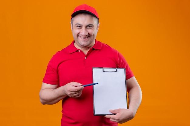 赤い制服を着ている配達人とそれをペンで指しているクリップボードを持ったキャップが前向きで幸せな笑顔で立っている笑顔 無料写真