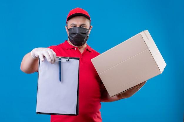 青いスペースの上に立っている深刻な顔でクリップボードと段ボール箱を保持している顔の防護マスクに赤い制服とキャップを身に着けている配達人 無料写真