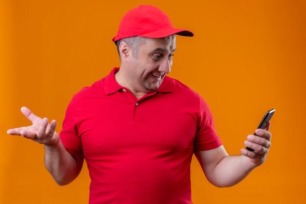 オレンジ色の壁に上げられた手で驚いて見ている携帯電話で赤い制服とキャップを身に着けている配達人 無料写真