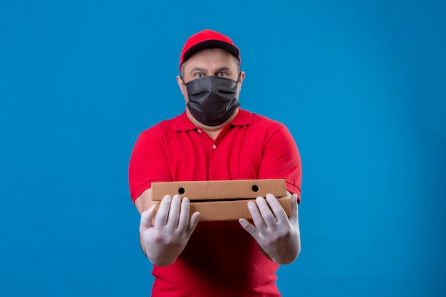 Delivery man wearing red uniform and cap in facial protective mask holding pizza boxes looking surprised with fear expression standing over blue space Free Photo