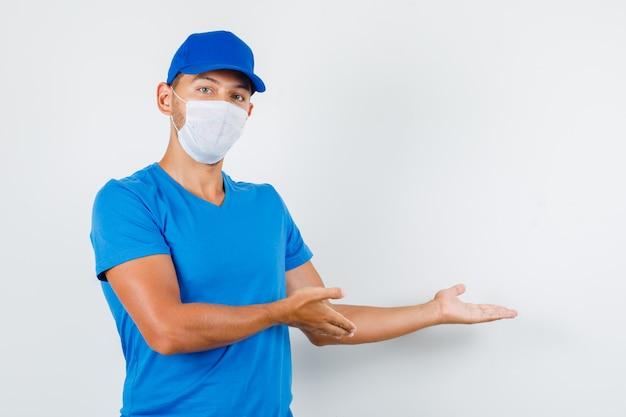 Доставщик приветствует или показывает что-то в синей футболке Бесплатные Фотографии