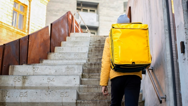 Delivery man at winter with yellow backpack climbing the stairs Free Photo