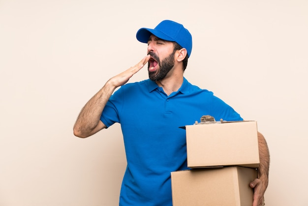 Delivery man with beard over isolated wall yawning and covering wide open mouth with hand Premium Photo
