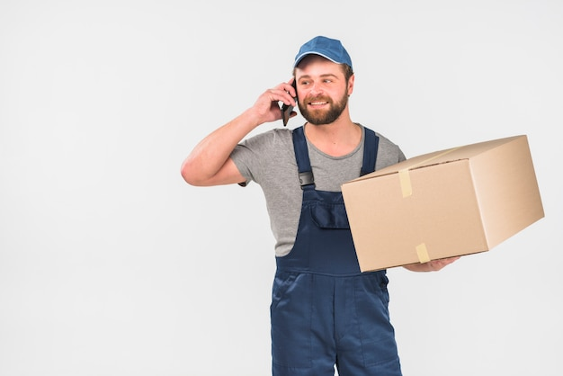 Delivery man with big box talking by phone Free Photo