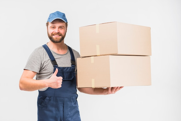 Delivery man with boxes showing thumb up Free Photo