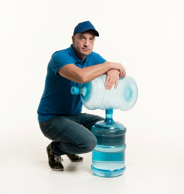Delivery man with cap posing with water bottles Free Photo