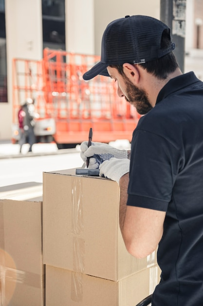 Delivery man with cardboard boxes writing on clipboard Free Photo