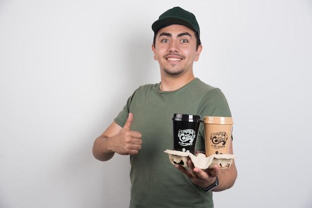 흰색 바탕에 엄지 손가락을 만드는 커피 컵과 배달 남자. 무료 사진