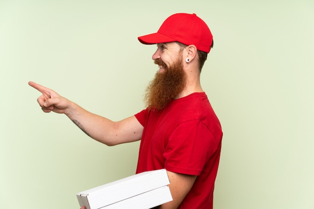 Delivery man with long beard over isolated green background pointing to the side to present a product Premium Photo