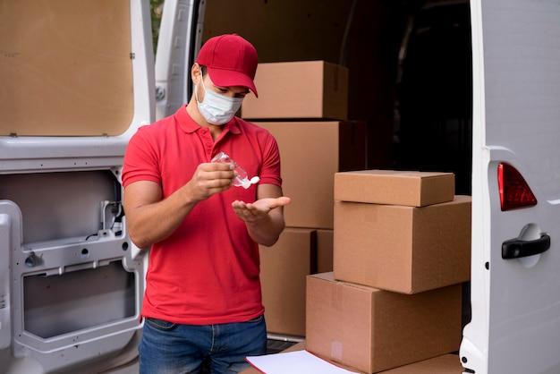 手の消毒剤を使用してマスクを持つ配達人 Premium写真