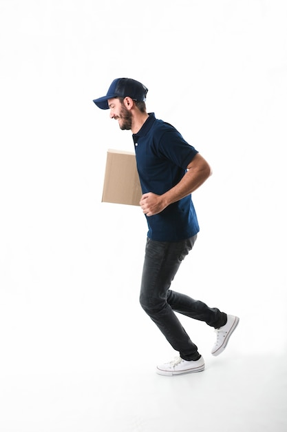 Delivery man with parcel running on white background Free Photo
