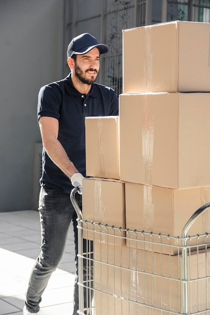 Delivery man with parcels walking on sidewalk Premium Photo