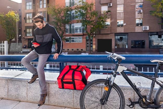 빨간 가방과 앉아있는 자전거를 가진 배달원, 그의 휴대 전화를 사용하여 자전거로 다음 주문을하십시오. 프리미엄 사진