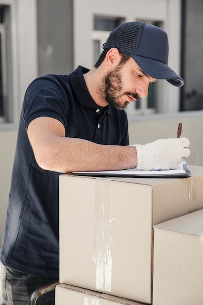 Delivery man writing on clipboard over stacked cardboard boxes Free Photo