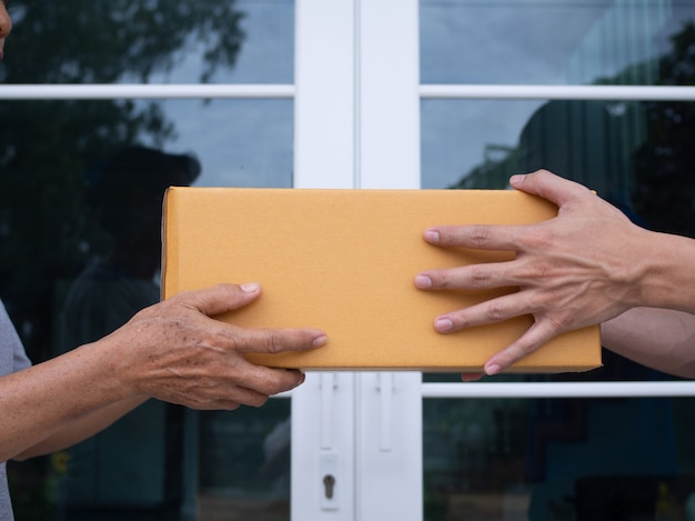 The delivery person is sending the parcel box to the recipient. Premium Photo