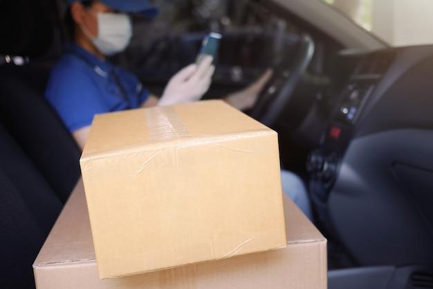 Курьер службы доставки во время пандемии коронавируса (covid-19), картонные коробки на сиденье фургона с водителем-курьером в размытом виде, в медицинской маске и латексных перчатках с телефоном Premium Фотографии