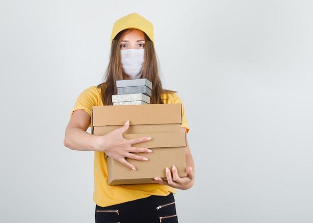 Donna di consegna che abbraccia scatole in t-shirt, pantaloni e berretto, maschera e sembra allegra Foto Gratuite
