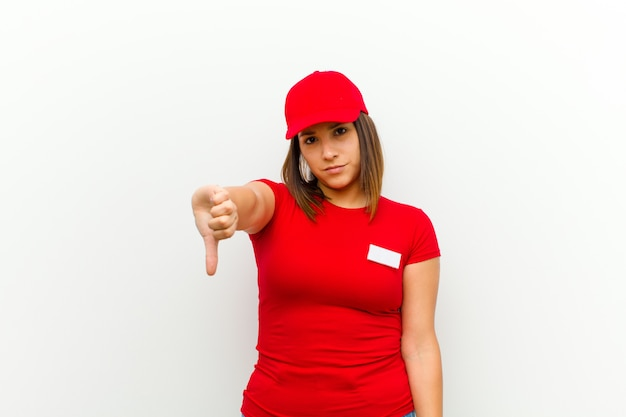 Delivery woman feeling cross, angry, annoyed, disappointed or displeased, showing thumbs down with a serious look against white Premium Photo