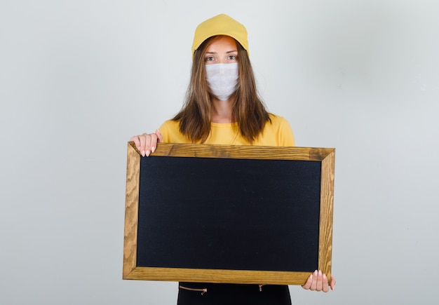 Tシャツ、ズボン、キャップ、マスクで黒板を保持している配達の女性 無料写真