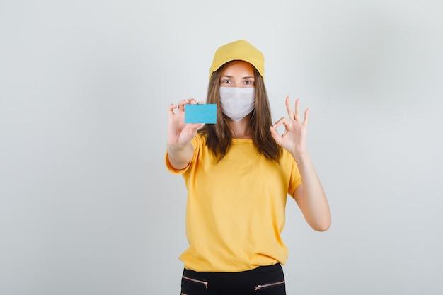 Tシャツ、ズボン、帽子、マスク、嬉しそうに見えるokサインと青いカードを保持している配達の女性 無料写真