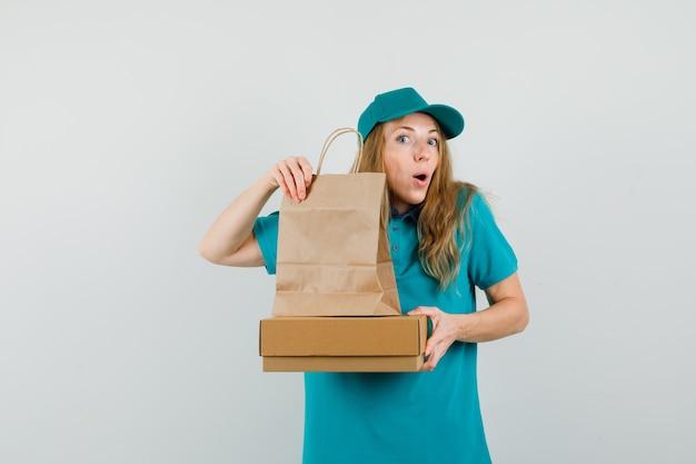Женщина-доставщик, держащая картонную коробку и бумажный пакет в футболке, кепке и любопытно глядя. Бесплатные Фотографии