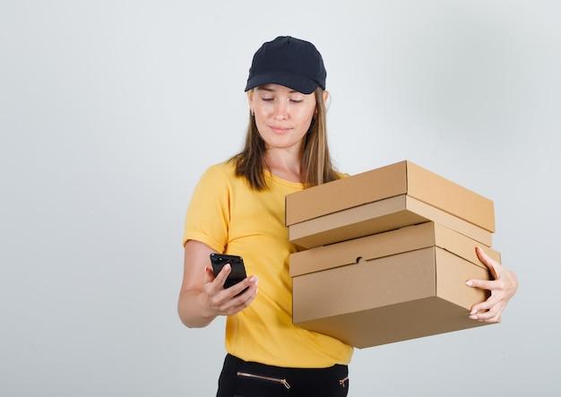 段ボール箱を持って、tシャツ、ズボン、帽子でスマートフォンを使用して配達女性 無料写真