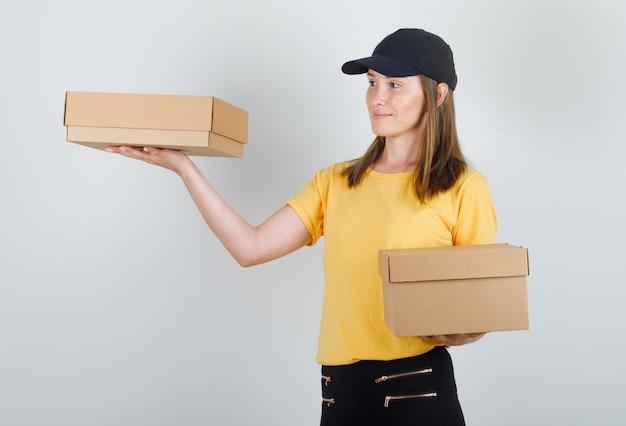 Tシャツ、ズボン、帽子の段ボール箱を保持している配達の女性 無料写真