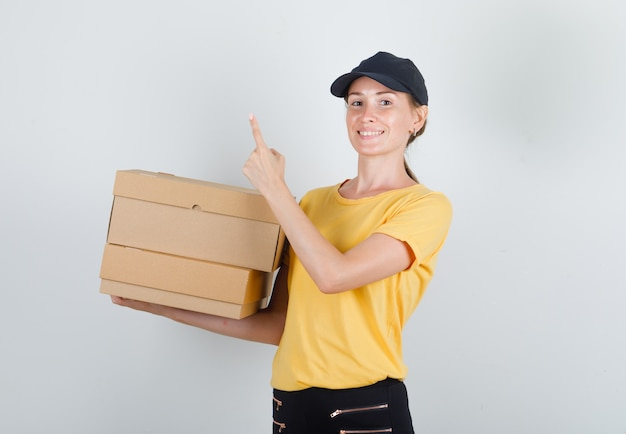 Tシャツ、ズボン、帽子で指を上げて段ボール箱を保持し、陽気に見える配達女性 無料写真