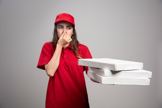 ピザの箱を運びながら鼻をしっかりと握る出産女性。 無料写真
