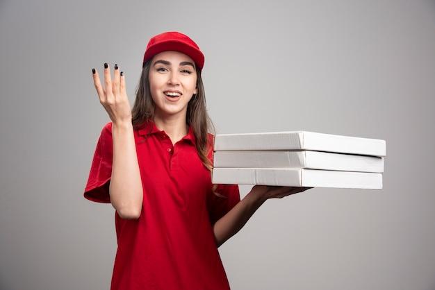 灰色の壁にピザを持っている配達の女性。 無料写真