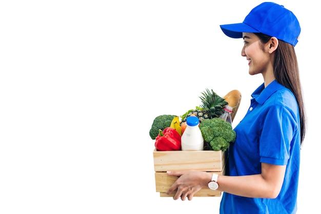 Доставщик в синей форме, несущей пакет продуктовых продуктов с овощами и фруктами на белом фоне Premium Фотографии