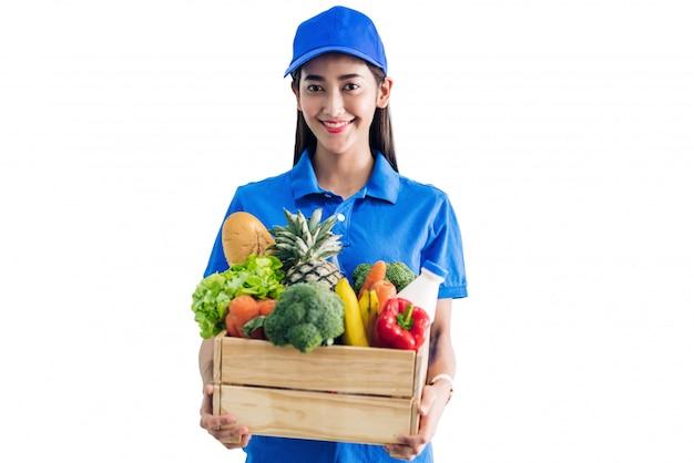 Доставка женщина в синей форме, перевозящих пакет продуктов питания с овощами и фруктами на белом изолированные Premium Фотографии